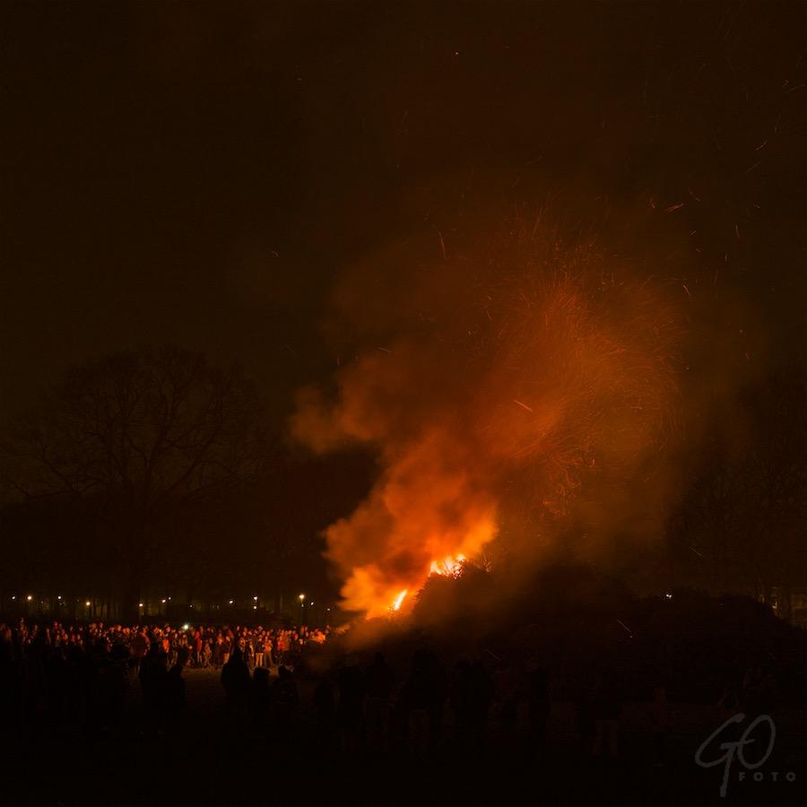 Foto van kerstbomenverbranding op het evenemententerrein in Hoogland. De lucht kleurt vuurrood.