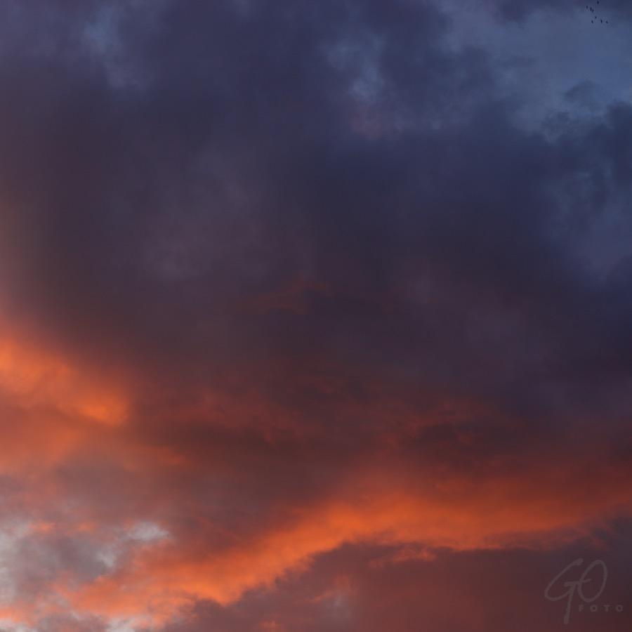 Wolkenman. Foto van een dreigende lucht met oranjerode tekening.