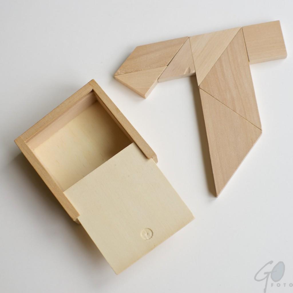 Gepuzzel met Tangram. Foto van een houten doosje met een houten spel Tangram.