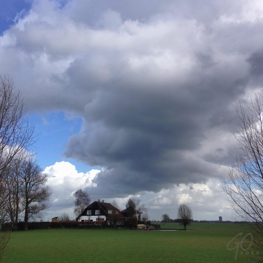 Wolkenstraten. Foto van een boerderij in de Eempolder.