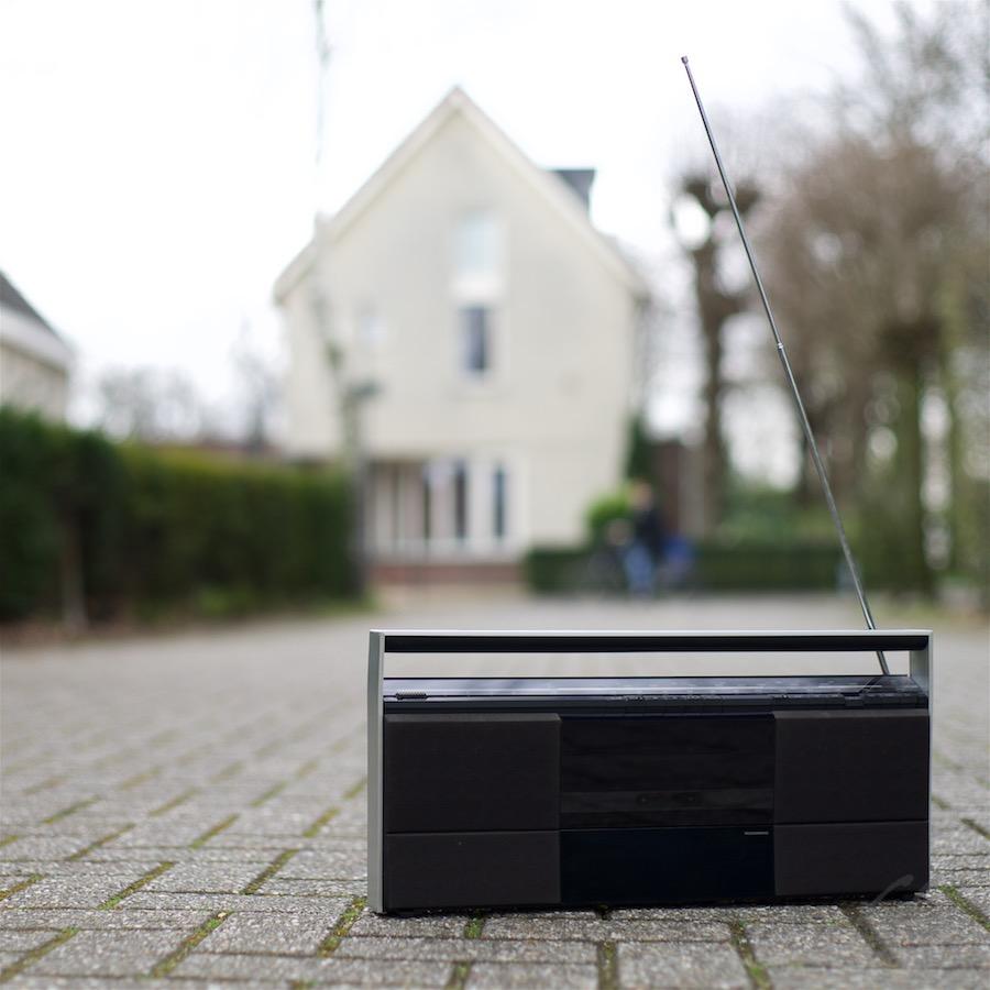 Radio is een vriendje. Foto van een transistorradio op een klinkerweg. Op de achtergrond een onscherp huis.