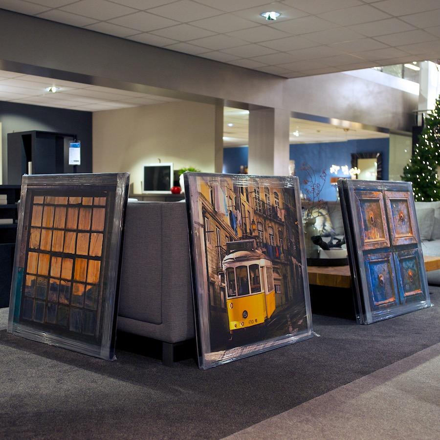 De eigenwaarde van een fotograaf. Drie ingelijste foto's bij een toonbank. Kok-wooncenter in Hoogland.