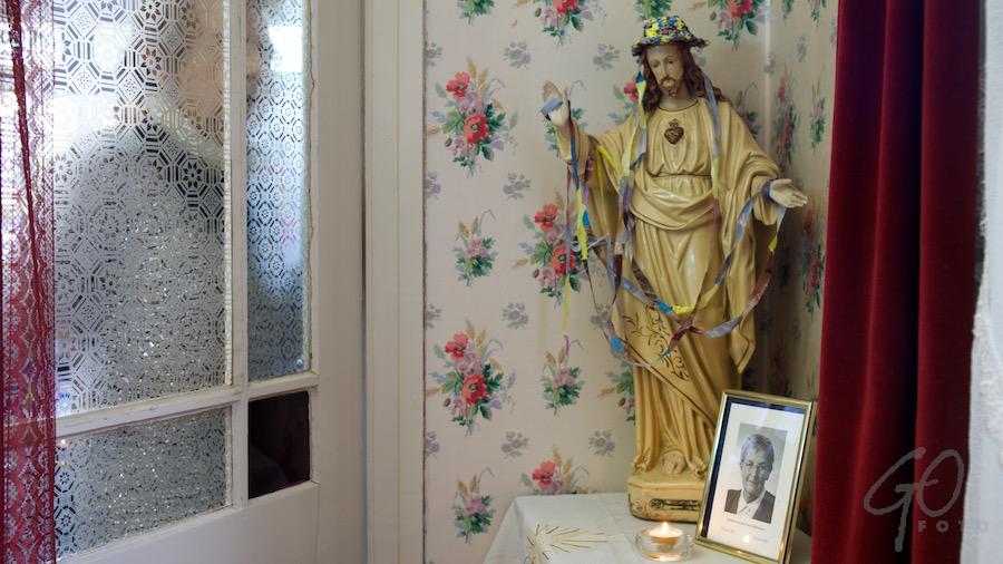 Fotografencafé Wat vertelt een foto eigenlijk Jezusbeeld in kamertje met bloemetjesbehang.