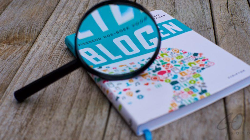 Tekstschrijvers en lezers willen structuur in een verhaal. Foto van een boek met een vergrootglas dat het woord 'blog' er uit licht.