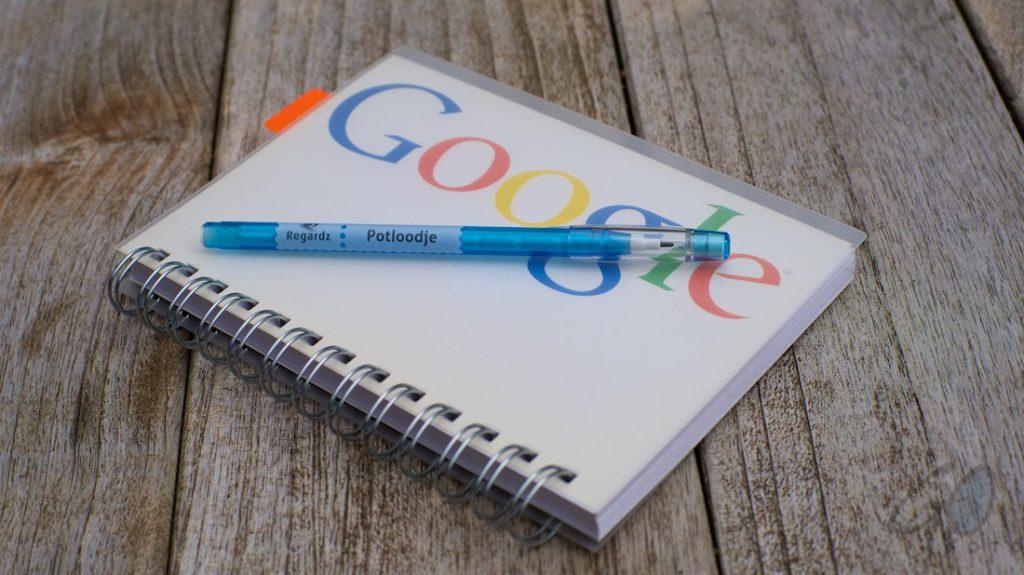 Tekstschrijvers en lezers willen structuur in een verhaal. Foto van notitieblok van Google met blauwe pen.
